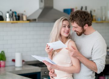 Casual loving couple at home checking the mail and looking very happy - lifestyle concepts